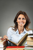 Smiling woman among books Royalty Free Stock Photos