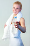 Smiling woman with a bottle of water and a towel Royalty Free Stock Photo