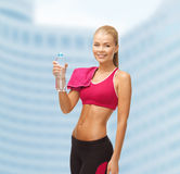 Smiling woman with bottle of water and towel Stock Images