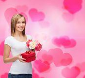 Smiling woman with bouquet of flowers and gift box stock image