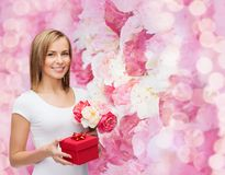 Smiling woman with bouquet of flowers and gift box Stock Photos