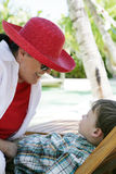 Smiling woman and boy. Adult woman in red hat smiling at a boy, outdoor, caucasian/white Royalty Free Stock Photos