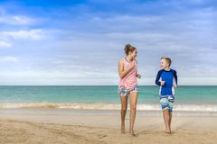 Smiling woman and boy running together on a beautiful beach on vacation royalty free stock photography