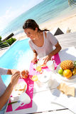 Smiling woman at breakfast table by the beach Royalty Free Stock Image