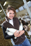 Smiling woman breeder with freshly collected bottles of milk royalty free stock photos