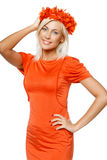 Smiling woman in bright orange dress wearing orange wreath Royalty Free Stock Images