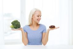 Smiling woman with broccoli and donut at home Royalty Free Stock Photos
