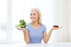 Smiling woman with broccoli and donut at home Royalty Free Stock Photo