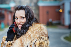 Smiling woman in brown coat with phone Royalty Free Stock Photos