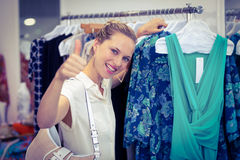 Smiling woman browsing clothes and thumbs up Royalty Free Stock Photo
