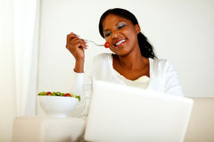 Smiling woman browsing the internet eating a salad Royalty Free Stock Photography