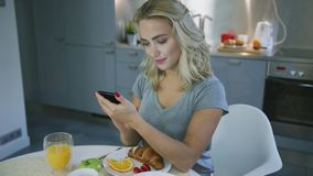 Smiling woman browsing smartphone during breakfast. Charming young woman in gray T-shirt using smartphone and smiling while having breakfast in stylish kitchen stock footage