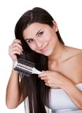 Smiling woman brushing long brunette hair Stock Photos