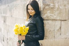 Smiling woman with a bunch of flowers. Sunny day royalty free stock photo