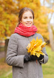 Smiling woman with bunch of leaves in autumn park Stock Images