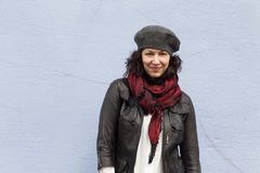 Smiling woman bundled up in stylish clothes. For winter, in front of blue background stock images