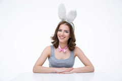 Smiling woman with bunny ears sitting at the table Stock Photos