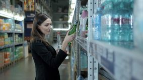 Smiling woman buying a bottle of water in grocery section of supermarket, businesswoman shopping