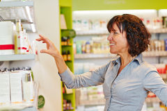 Smiling woman buying cosmetics in supermarket Stock Photos