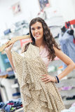Smiling Woman Buying a Dress Stock Photos