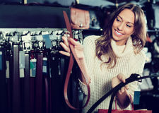 Smiling woman buying leather belts at shop Stock Photo