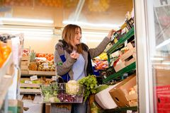 Smiling woman buying vegetables Stock Photo