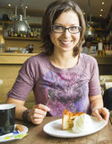 Smiling woman at cafe eating apple cake dessert with cream Stock Images