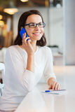 Smiling woman calling on smartphone at cafe Stock Photos