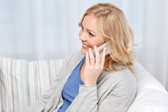 Smiling woman calling on smartphone at home. People, technology and communication concept - smiling woman calling on smartphone at home Royalty Free Stock Photos