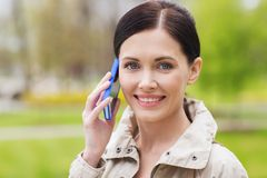 Smiling woman calling on smartphone in park Royalty Free Stock Photo