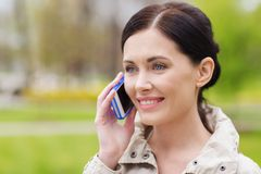 Smiling woman calling on smartphone in park Royalty Free Stock Images