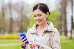 Smiling woman calling on smartphone in park Royalty Free Stock Image