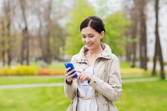 Smiling woman calling on smartphone in park Royalty Free Stock Photos