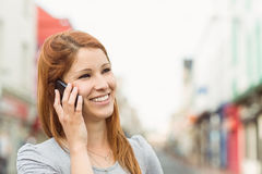 Smiling woman calling someone with her mobile phone Royalty Free Stock Photo