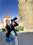 The smiling woman with the camera photographs old city wall towers. Tallinn, Estonia Royalty Free Stock Photos