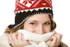 Smiling woman with cap holding scarf over mouth Stock Photo