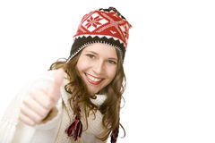 Smiling woman with cap and scarf shows thumb up Royalty Free Stock Photography