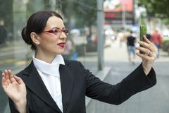 Smiling Woman Capturing A Self Shot. Smiling business woman Capturing on street Stock Photo
