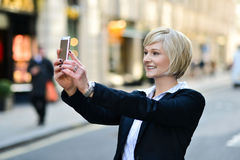 Smiling woman capturing a self shot. Corporate lady clicking her pic, outdoors Stock Photography