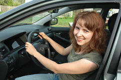 Smiling woman in car. Smiling young woman sat in driving seat of car with open door holding steering wheel stock image