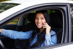 Smiling woman in the car and calling Royalty Free Stock Photos