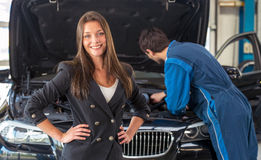 Smiling woman in a car servicing garage Royalty Free Stock Photo