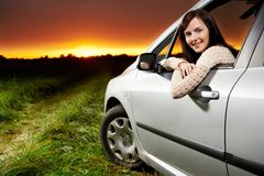 Smiling woman in the car at sunset Stock Photos
