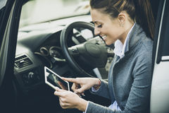 Smiling woman in a car with tablet royalty free stock image