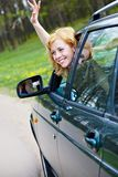 A smiling woman in a car is wagging Royalty Free Stock Photos