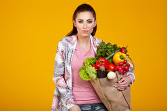 Smiling woman carrying a bag with vegetables Royalty Free Stock Images