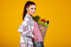 Smiling woman carrying a bag with vegetables Stock Images