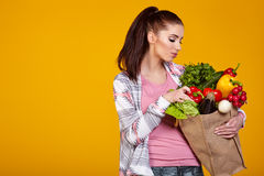 Smiling woman carrying a bag with vegetables Stock Photos