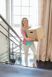 Smiling woman carrying cardboard box while moving up steps at new home Stock Image