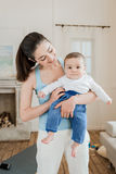 Smiling woman carrying her happy baby child on arms at home Royalty Free Stock Photo